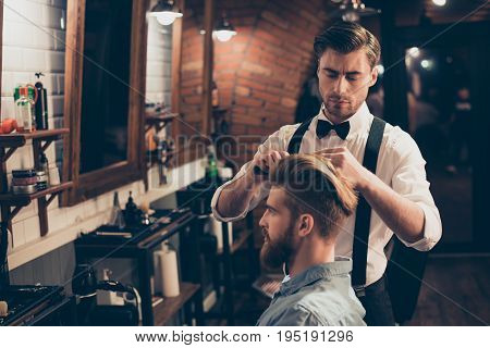 Young Stylish Bearded Guy Is In A Barber Shop, Getting Brend New Haircut From A Classy Dressed Styli