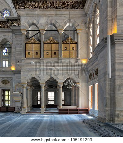 Istanbul, Turkey - April 20, 2017: Interior of Nuruosmaniye Mosque an Ottoman Baroque style mosque built in 1755 with arcades wooden doors windows and blue carpet located in Shemberlitash Fatih Istanbul Turkey