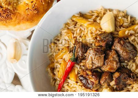 Uzbek Pilaf - Rice with Meat and Vegetables on the table. Pilaf with lamb and garlic zira. close up.