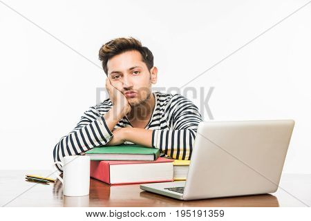 Handsome Indian boy or male college student studying on study table with pile of books, laptop computer and coffee mug. Smiling or thinking or worried or showing thumbs up or using smartphone