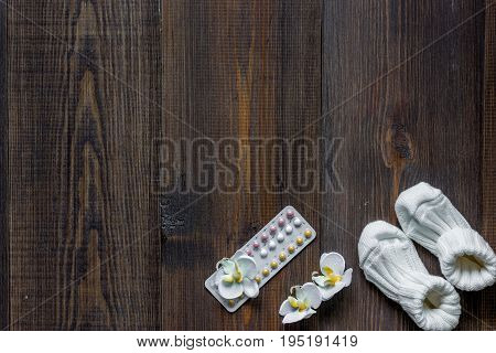 Female contraception pills on wooden background top view.