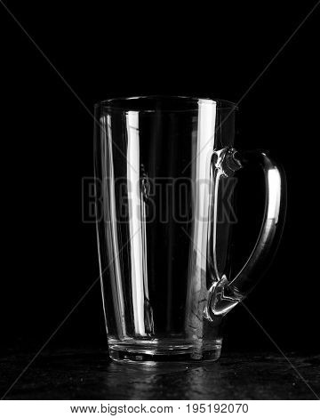 Large beer glass with white transparent glass handle. Dark wooden background. Side view.