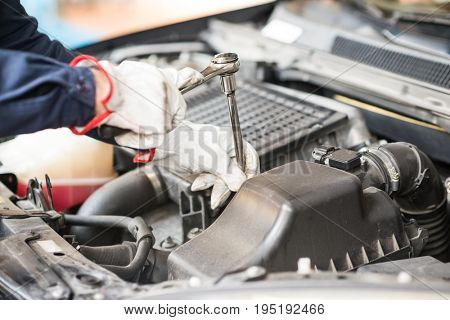 Detail of an auto mechanic at work on a car in his garage