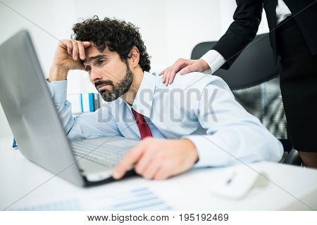 Sad businessman looking at a computer screen in his office