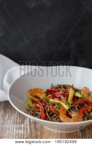 Noodles with vegetables and seafood on a wooden table Chinese-style noodles with vegetables and seafood. copy space