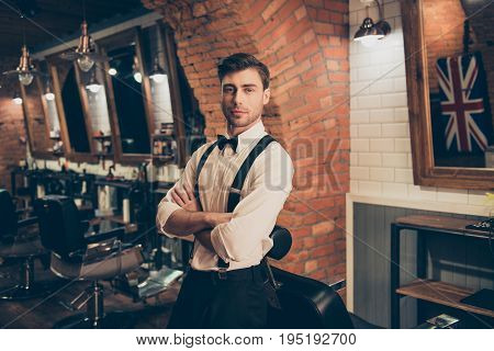 Welcome to barber shop! Attractive young brunette guy with bristle in a barber shop standing with crossed hands dressed classy in a retro style. Looking hot and flirty