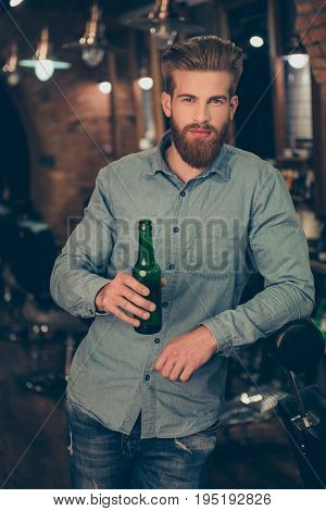 Casual Men`s Life. Handsome Stylish Young Red Bearded Man In A Casual Jeans Outfit Is Drinking Beer,