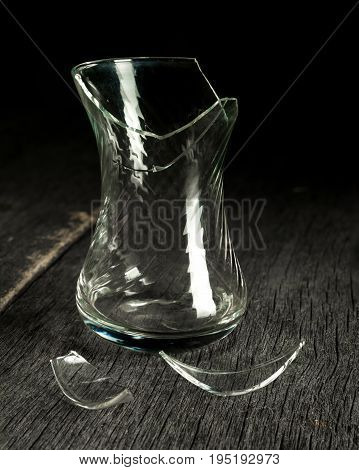 Broken glass glass and shards on a gray wooden background. Low key. Side view.