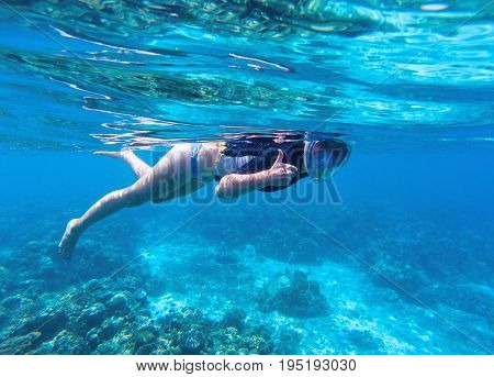 Woman snorkeling in blue water. Snorkel shows thumb in full face mask. Summer activity. Beautiful girl in sea water. Underwater photo of oceanic landscape. Seaside adventure. Water sport in tropic sea