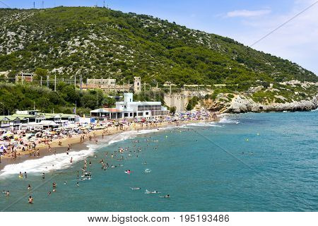 SITGES, SPAIN - JULY 9, 2017: People enjoying, relaxing, sunbathing or bathing at the Garraf Beach in Sitges, a popular beach in the coast of the Metropolitan Area of Barcelona, in Catalonia