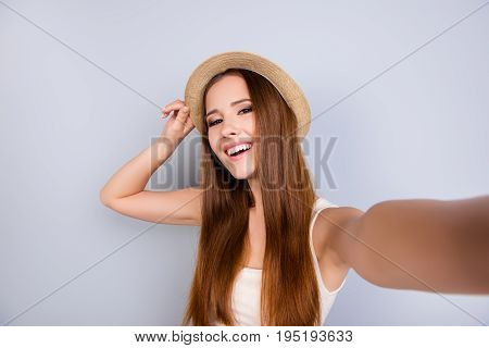 Young Cheerful Attractive Brown-haired Lady Is Smiling On The Light Blue Background. She Is Taking S