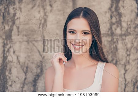 Close Up Of Young Gorgeous Girl Standing On The Background Of Concrete Wall Outdoors And Smiling, We