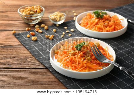 White plates with yummy carrot raisin salad with pine nuts on black checkered napkin