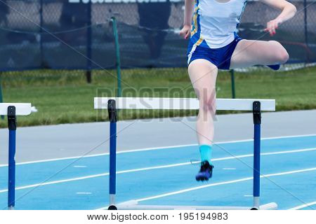High school girl is racing the 400 meter hurdles on a blue track outside