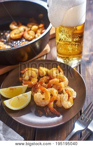 Rustic still life with shrimps in plate next to glass of beer on wooden table. Vertical shot.S