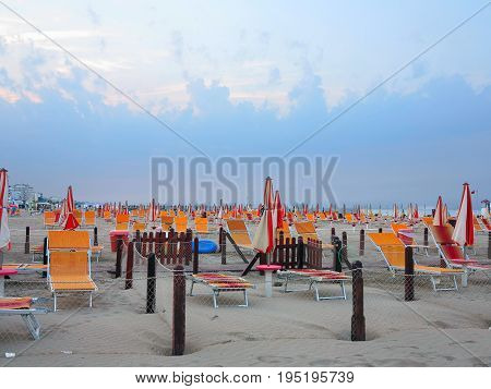 Comfortable sand beach with sun beds and orange umbrellas