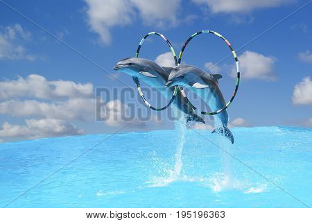 Jump the two large bottlenose dolphins bottlenose Dolphin (lat. Tursiops truncatus) through the Hoop over the water on the background of blue sky with clouds