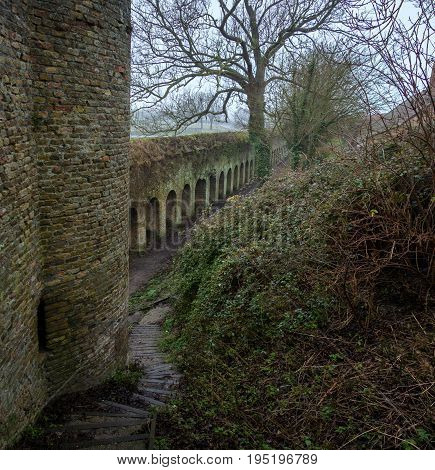 The old fortress wall and a fragment of the tower, green with time. City of Bergues, France. In the foreground is a overgrown hillside and a stone staircase.