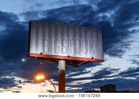 Empty blank iron billboard against the background of evening dramatic sky