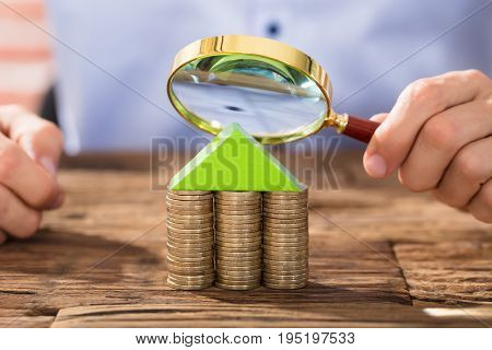 Close-up Of A Person Holding Magnifying Glass Over The House Made With Coin Stack