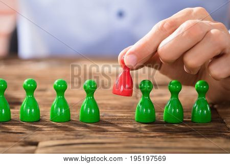 Close-up Of A Person Placing Red Figures In The Green Row Over The Wooden Desk