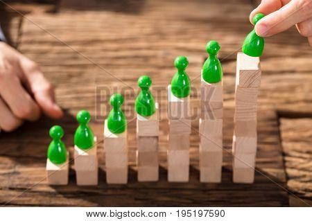 Businessman Arranging The Green Figures On Increasing Wooden Block Stack