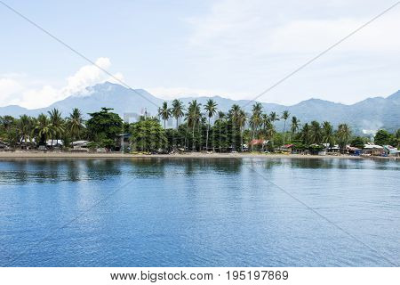 Seaside landscape with still blue water and tropical island. Sea view with distant island. Green palm trees reflecting in seawater. Sea and sky minimal photo background. Idyllic seashore village view