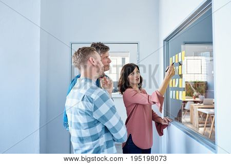 Three casually dressed focused office colleagues brainstorming on a window with sticky notes window standing together in a modern office