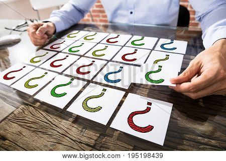 Businessman With Colorful Question Mark On Adhesive Notes Over The Desk In Office