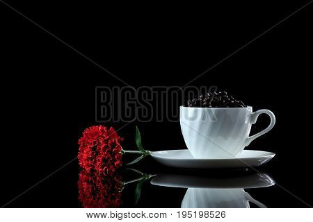 Cup With Coffee Beans And Red Carnation On A Black Reflective Background