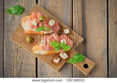 Bruschetta with smoked salmon cream cheese olives and rucola on wooden plate. Sandwiches with salted fish. Flat lay. Top view with space for text.