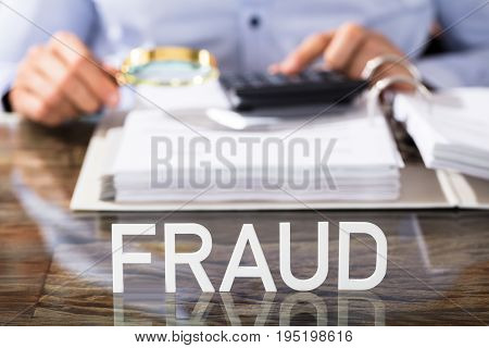 Close-up Of Financial Data Analyst With Fraud Text On Glass Desk In Office