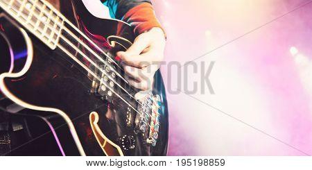 Closeup of man playing bass guitar at concert
