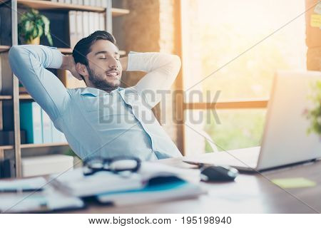 Well Done! Young Cheerful Middle Eastern Guy Realtor Is Resting At A Workplace, Smiling And Enjoying