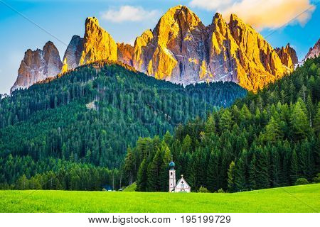 Magnificent serrated cliffs illuminate the summer sunset. Chapel of St. Mary Magdalene and the bell tower in the valley of the Dolomites. The concept of eco-tourism in Tirol