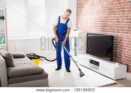 Smiling Young Male Janitor Vacuuming Carpet At Home