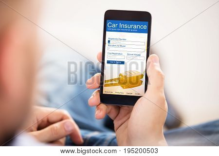 Close-up Of A Man Filling Car Insurance Form On Mobile Phone