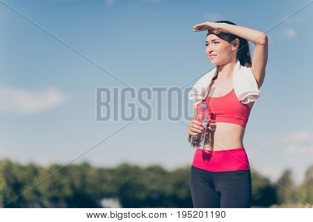 Young Fit Sportwoman Finished Her Work Out And Now Drinking Water And Smiling. She Is Outside On A S