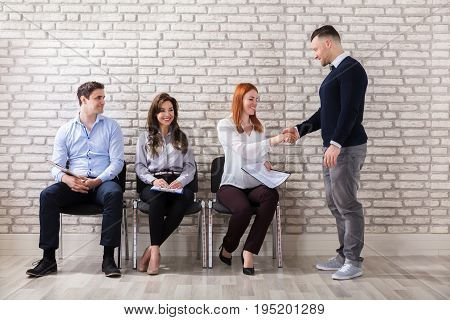 Young Applicant Woman Shaking Hands With Businessman In Office
