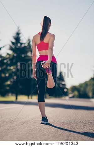 Rear View Of Lady Trainer, Stretching Her Legs By Doing Exercise. She Is Training Outdoors On A Summ