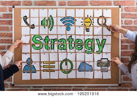 Business People Hands Making Strategy Concept With Adhesive Notes On Corkboard