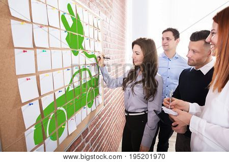 Group Of Business People Planning Eco Car On Adhesive Notes Over The Corkboard