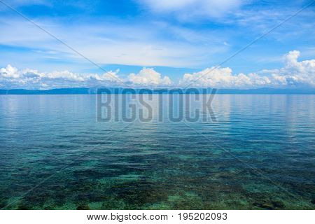 Sea landscape with clouds. Peaceful blue seascape. Tropical seaside minimal photo for wedding background. Peaceful cumulus on horizon. Tropical climate or weather change. Tropical sea island landscape