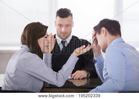 Young Couple Arguing With Each Other In Front Of Judge At Courtroom