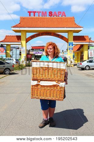 PRAGUE CZECH REPUBLIC - JULY 13, 2017: Unidentified shopper with baskets against Gate to asian market TTTM SAPA and Vietnamese town in Prague suburban district Libus.