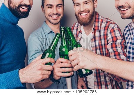 Cheers men! Bachelor men`s life. Low angle cropped photo of four happy friends clinking their glasses of beer. They are fans of sports games as football basketball hockey baseball