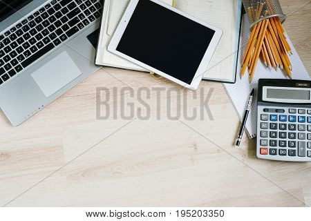 Work office desk table with laptop, tablet, supplies and calculator. Top view with copy space, flat lay finance background