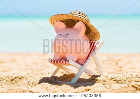 Pink Piggy Bank With Straw Hat Kept Over The Deck Chair At Beach