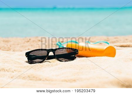 Black Sunglasses Sunscreen Lotion And Slippers On The Sand At Beach In Summer