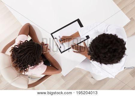 High Angle View Of Doctor And Patient Sitting In Clinic With Clipboard